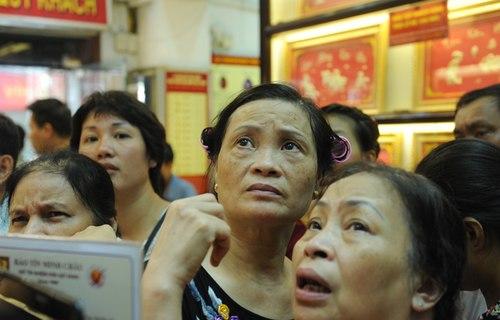 Người mua theo dõi giá vàng trên bảng trong lúc chờ đến lượt