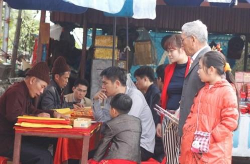 Một gia đình đang xin sớ trước cổng đền Trần