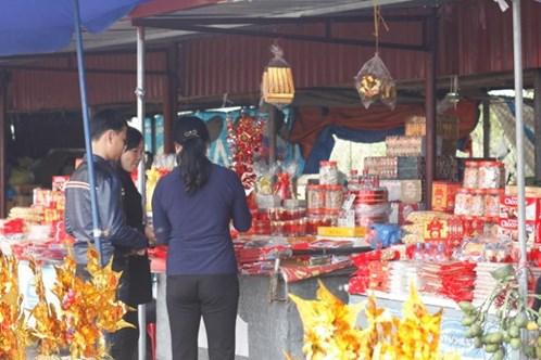 Khách du lịch đang mua lộc, đèn cầy, giấy vàng bạc trước khi vào cúng đền.
