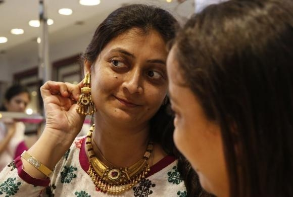 Woman tries on a gold earring inside a jewellery showroom at a market in Mumbai