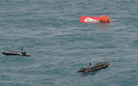Đội thợ lặn đang hỗ trợ trục vớt đuôi máy bay QZ8501 (ảnh: AP)
