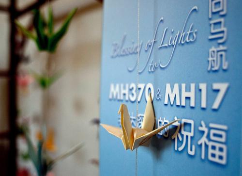 Hạc giấy treo trên tấm bảng ghi lời cầu nguyện và chia buồn tới các nạn nhân MH370 và MH17 ở Kuala Lumpur, Malaysia hồi tháng 9/2014. Ảnh: AFP.